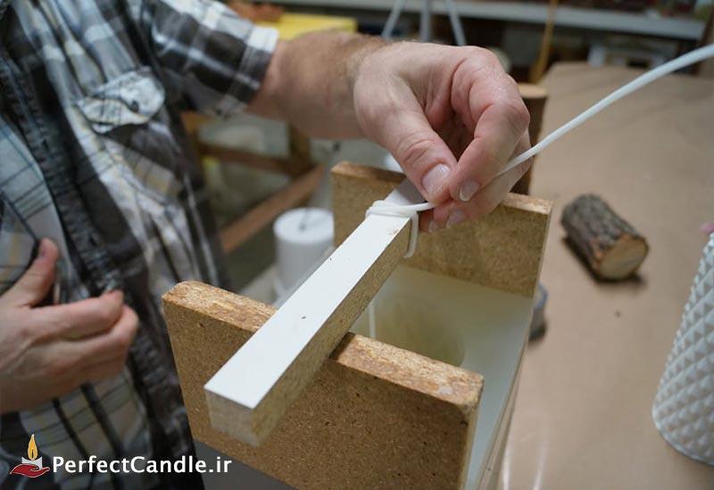 اضافه کردن فیتیله به انتهای قالب و عمود نگه داشتن فیتیله